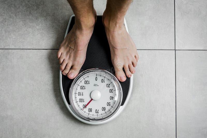A escala de peso do close-up, posição dos homens pesa sobre escalas fotos de stock