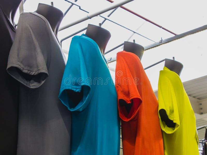 Escala de t-shirt coloridos da cor diferente em uma loja dos esportes PR imagem de stock