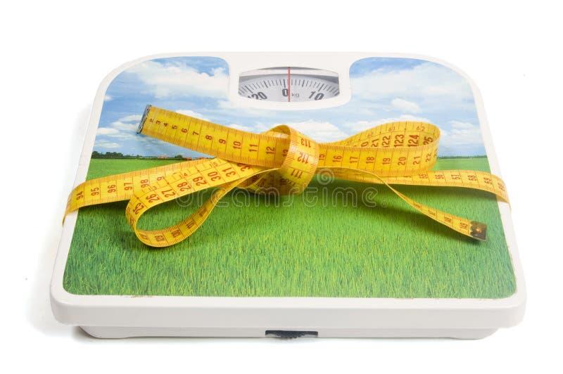Escala del peso con una cinta de la medida como cinta fotografía de archivo