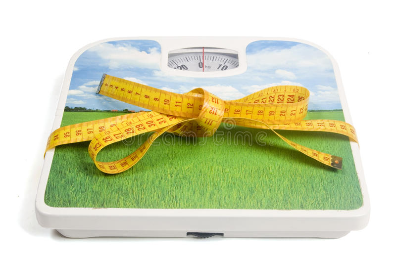 Escala do peso com uma fita da medida como uma fita fotografia de stock
