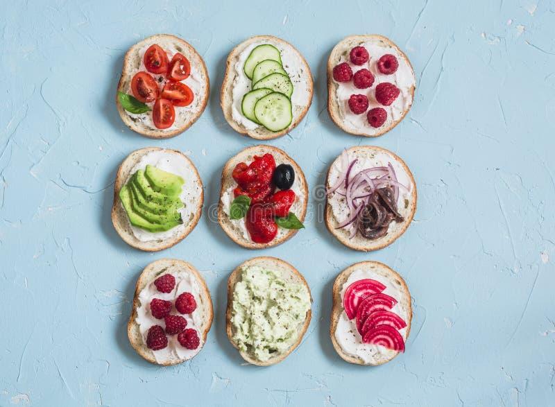 Escala dos sanduíches - os sanduíches com queijo, tomates, anchovas, roasted pimentas, framboesas, abacate, pasta do feijão, pepi imagens de stock royalty free
