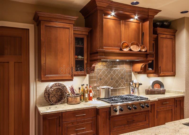 Escala e armários home da parte superior do fogão de cozinha na casa luxuosa nova imagens de stock royalty free
