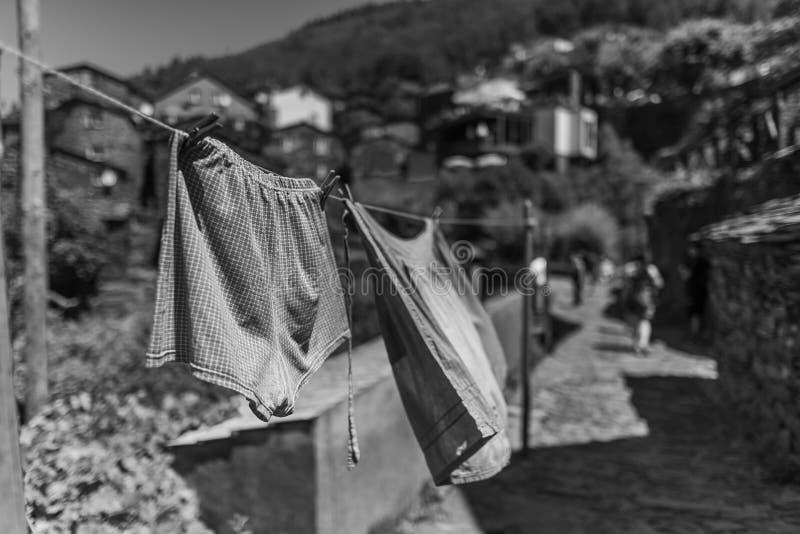 Escala griega de ropa lavada en la línea rodeada de edificios y colinas bajo el sol fotografía de archivo