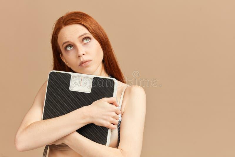 Escala hermosa de la tenencia de la mujer joven y pantalones demasiado grandes como ella perdi? el peso imagenes de archivo