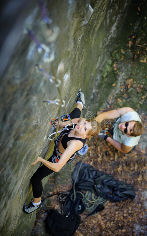 Escalada de la mujer con las carabinas y la cuerda fotografía de archivo