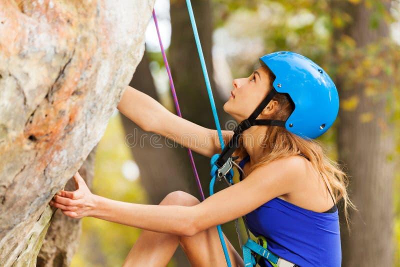 Escalada de la mujer joven al top de la montaña imagen de archivo