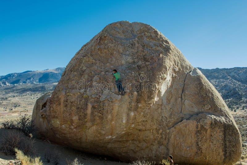 Escalada de la mujer un Boulder grande foto de archivo libre de regalías