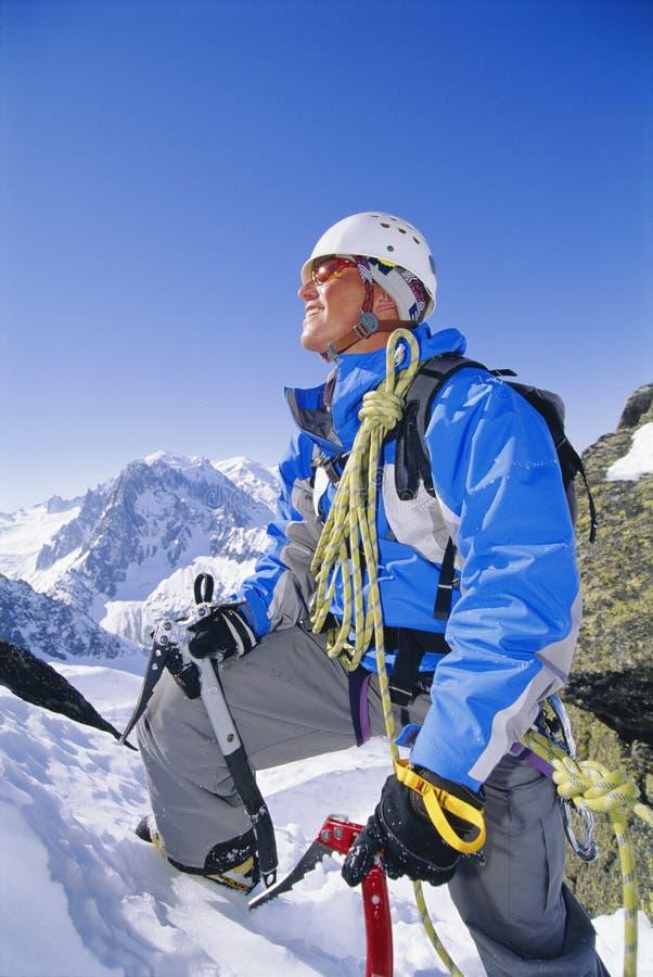 Escalada de montanha do homem novo no pico nevado fotografia de stock royalty free
