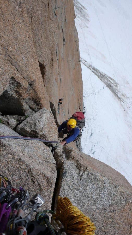 Escalada del hombre una ruta vertical escarpada de la escalada del granito en las montañas francesas cerca de Mont Blanc sobre el imagen de archivo libre de regalías