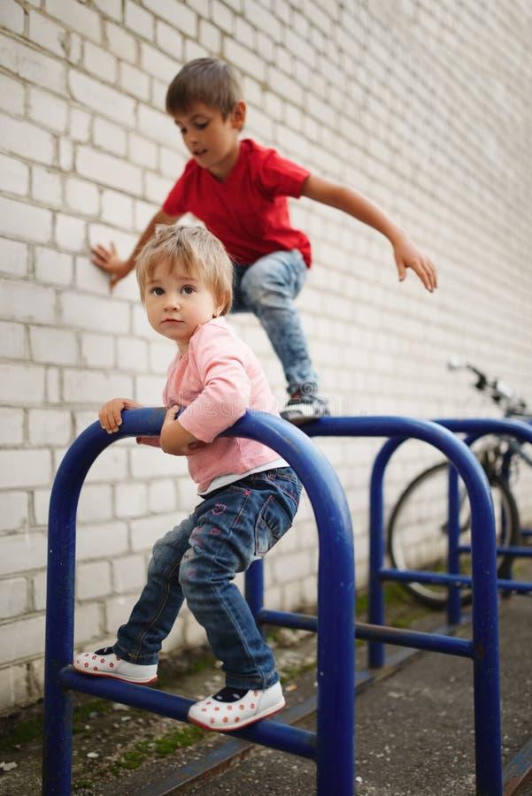 Escalada do menino e da menina no estacionamento da bicicleta imagem de stock royalty free