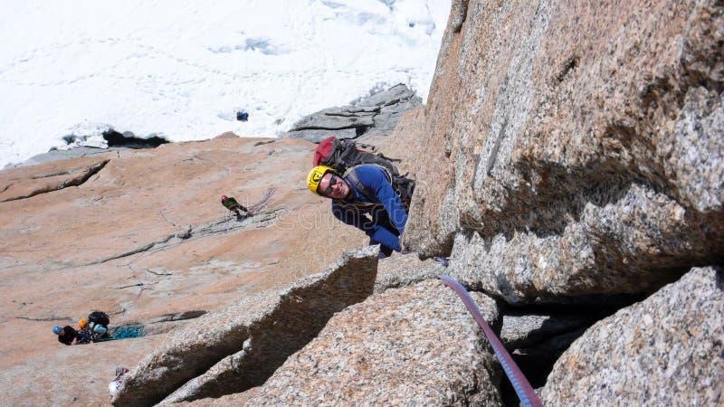 Escalada masculina una ruta vertical escarpada de la escalada del granito en las montañas francesas cerca de Mont Blanc sobre el  foto de archivo