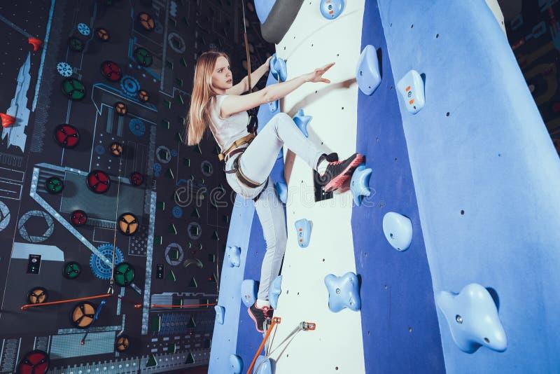 Escalada practicante de la mujer joven en la pared de la roca dentro foto de archivo libre de regalías