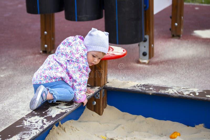 Escaladas do bebê na caixa de areia através do lado Uma menina joga no campo de jogos, escaladas na caixa de areia para jogar na  foto de stock