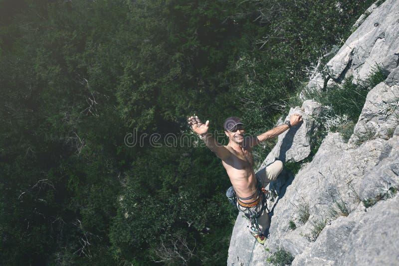 Escaladas do montanhista de rocha do homem no penhasco foto de stock royalty free