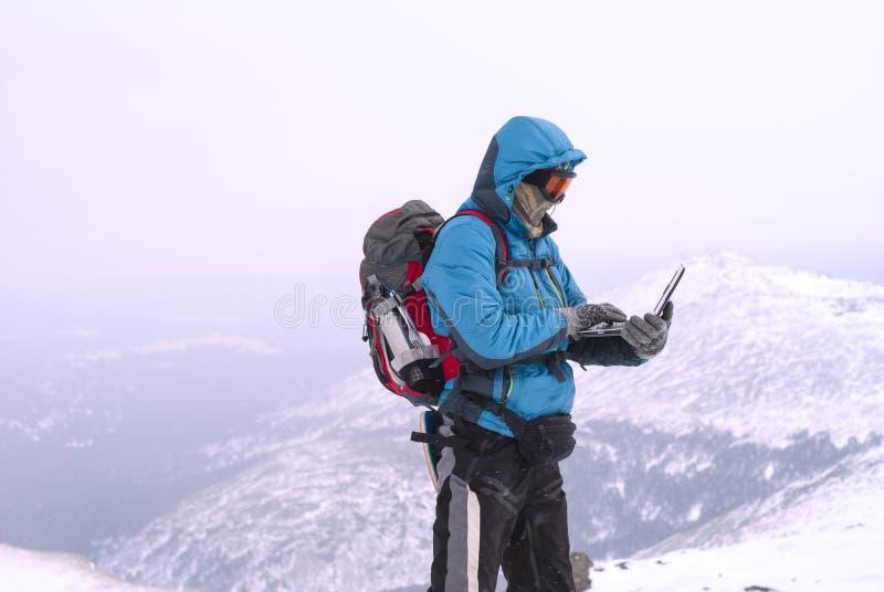 Escalador con un ordenador portátil en invierno encima de una montaña imagen de archivo