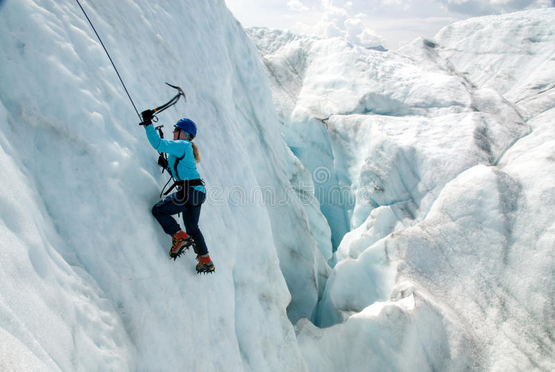 Escalador de hielo femenino en el glaciar de la raíz imagen de archivo