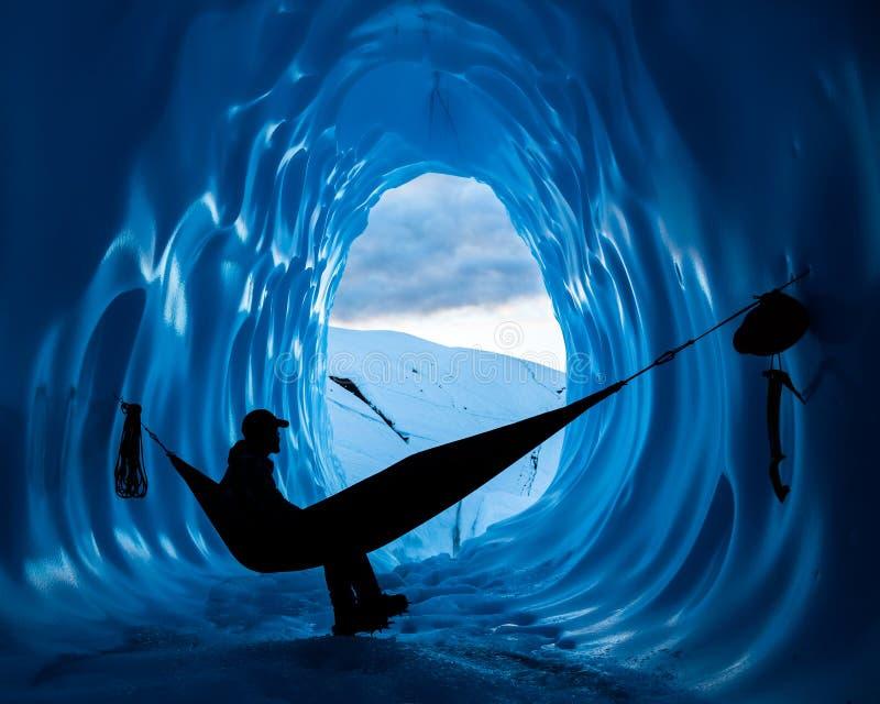 Escalador de hielo que descansa en hamaca dentro de una cueva de hielo azul profunda en el glaciar de Matanuska de Alaska foto de archivo