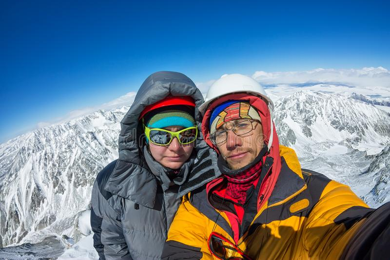 Escalador de los pares de Selfie en soporte del casco y abajo de la chaqueta encima de la montaña fotografía de archivo libre de regalías