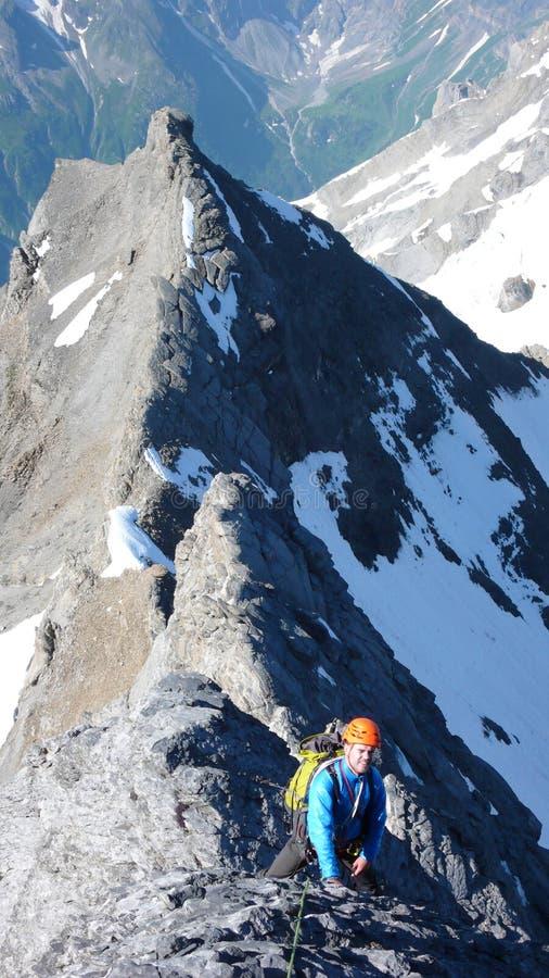 Escalador de montaña masculino en su manera a una alta cumbre alpina en un canto escarpado y expuesto de la roca en un día de ver foto de archivo libre de regalías
