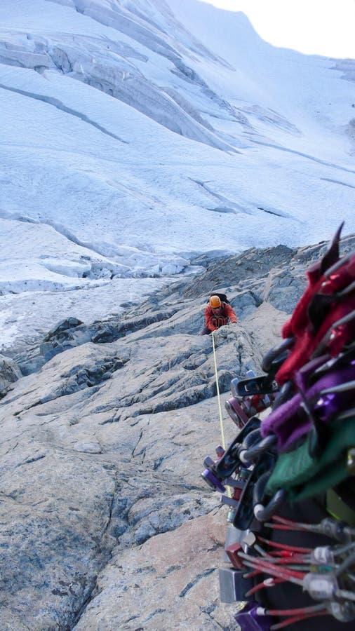 Escalador de montaña masculino en un alto expuesto de la ruta que sube sobre un glaciar fotos de archivo