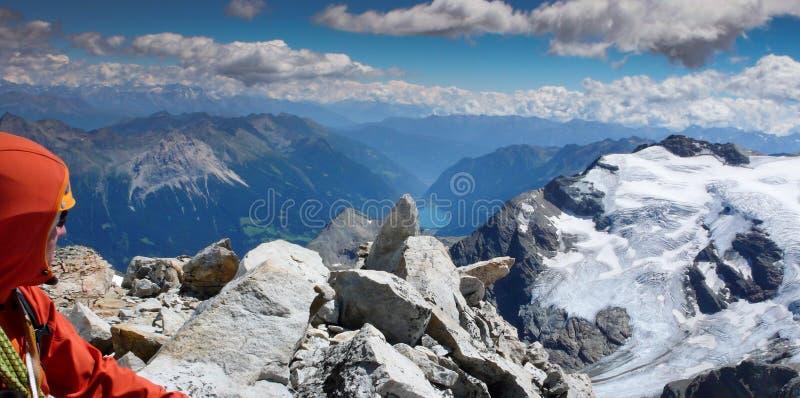 Escalador de montaña masculino en un alto pico de montaña alpino que admira la opinión y el panorama maravillosos del paisaje de  fotos de archivo libres de regalías