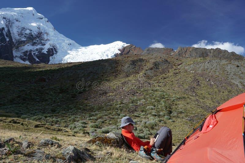 Escalador de montaña que se sienta fuera de una tienda y que escribe en su diario en el Blanca de Cordillera en Perú fotografía de archivo libre de regalías
