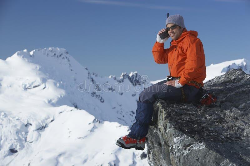 Escalador de montaña que usa el Walkietalkie contra pico de montaña imagenes de archivo