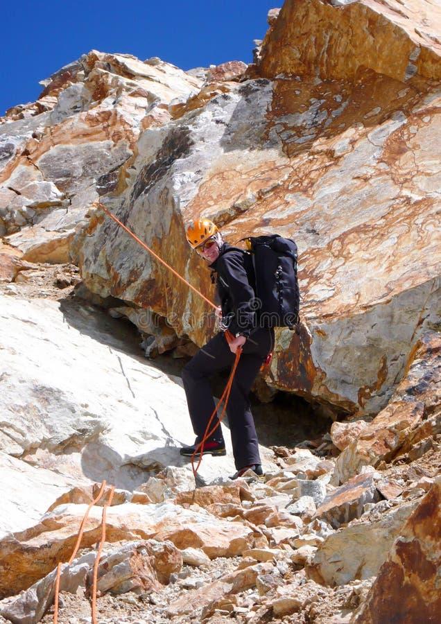Escalador de montaña rappelling abajo sobre rocas rojas en los altos picos y las montañas de las montañas suizas debajo de un cie foto de archivo