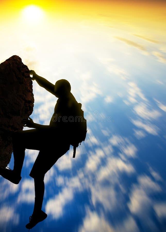 Escalador de roca en el fondo de la puesta del sol. foto de archivo