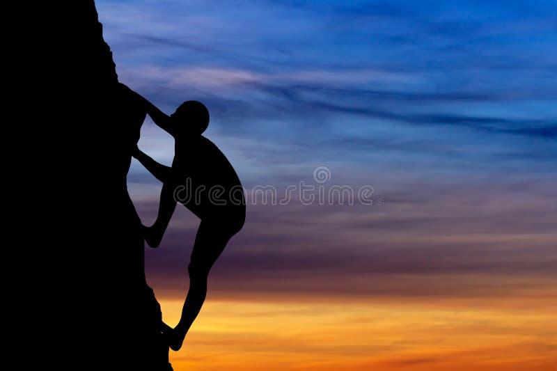 Escalador de roca en el fondo de la puesta del sol. fotografía de archivo libre de regalías