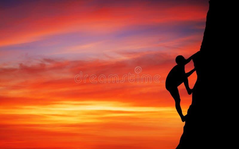 Escalador de roca en el fondo de la puesta del sol imagen de archivo