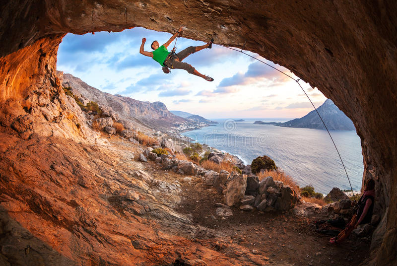 Escalador de roca masculino que sube a lo largo de un tejado en una cueva imágenes de archivo libres de regalías