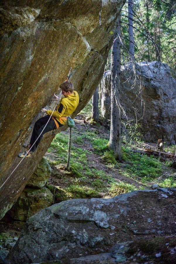 Escalador de roca que asciende un acantilado desafiador Climbi extremo del deporte fotos de archivo