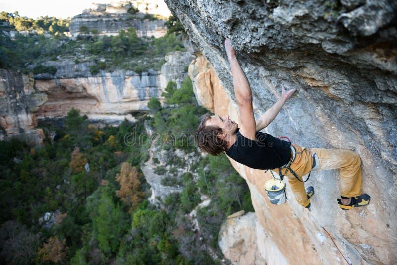 Escalador de roca que asciende un acantilado desafiador El subir extremo del deporte Libertad, riesgo, desafío, éxito imagen de archivo libre de regalías