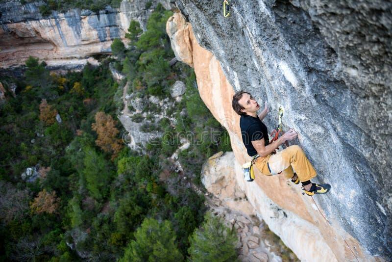 Escalador de roca que asciende un acantilado desafiador El subir extremo del deporte Libertad, riesgo, desafío, éxito Deporte y v fotografía de archivo libre de regalías