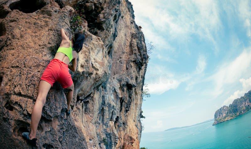 Escalador de roca que sube en el acantilado de la playa fotografía de archivo libre de regalías