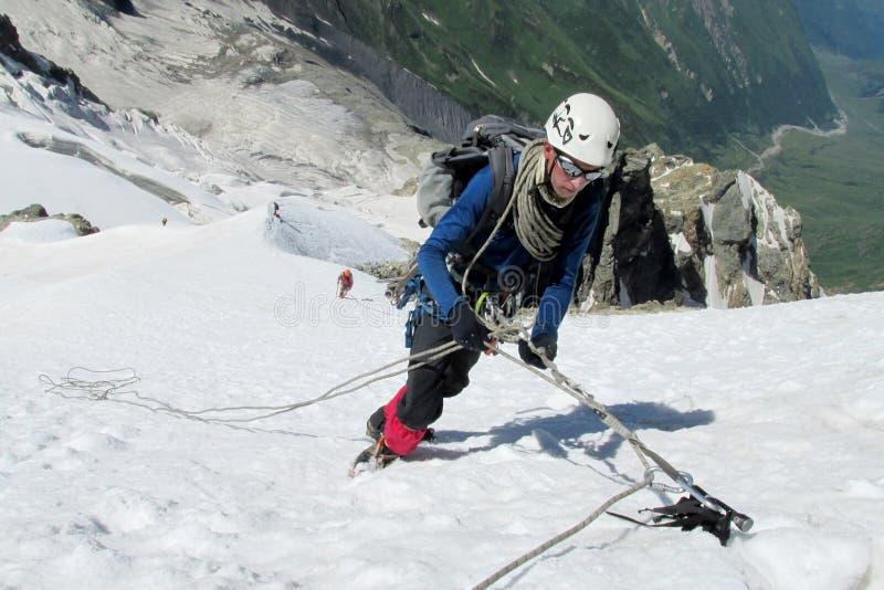 Escalador en cumbre de la nieve, picos de montaña rocosa y el glaciar foto de archivo