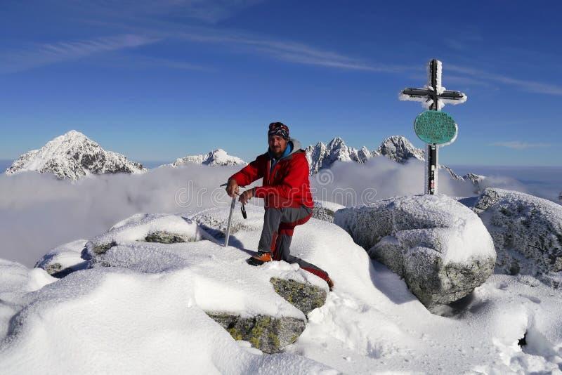 Escalador encima de la montaña en invierno imagenes de archivo