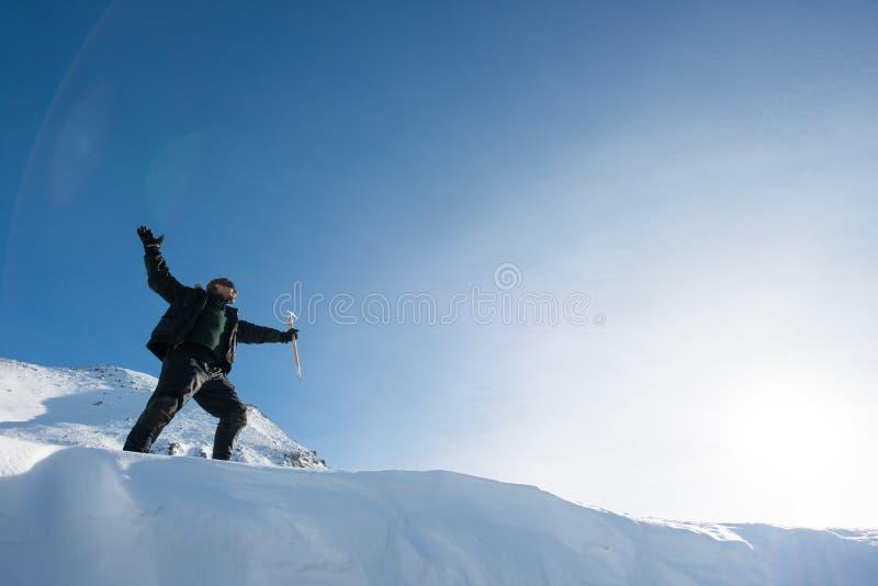 Escalador feliz con un hacha de hielo en las montañas nevosas fotos de archivo libres de regalías