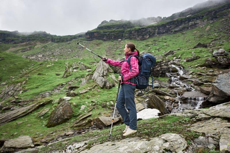 Escalador femenino joven que se coloca en el borde de la roca que admira el paisaje hermoso de montañas rocosas y de cuestas verd imagen de archivo