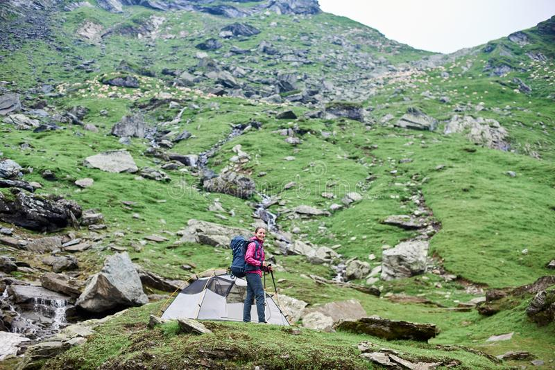 Escalador femenino joven que se coloca en roca cerca de la tienda en cuesta rocosa verde en montañas imagen de archivo libre de regalías