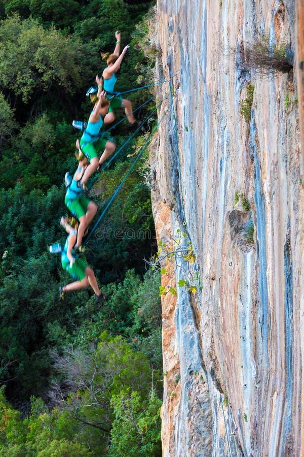 Escalador femenino que cae abajo del top de la alta pared rocosa colorida imagen de archivo