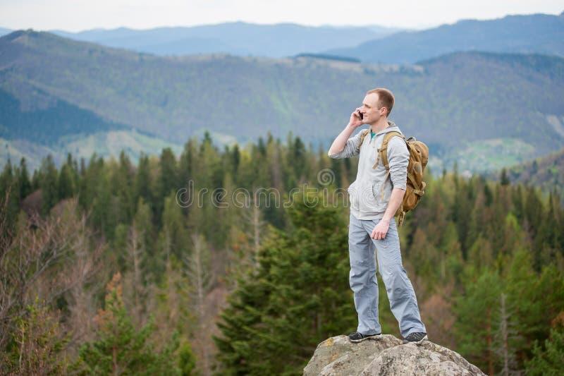 Escalador masculino con la mochila marrón en el pico de la roca fotografía de archivo