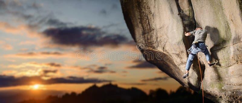 Escalador masculino que sube el canto rodado grande en naturaleza con la cuerda imagen de archivo libre de regalías