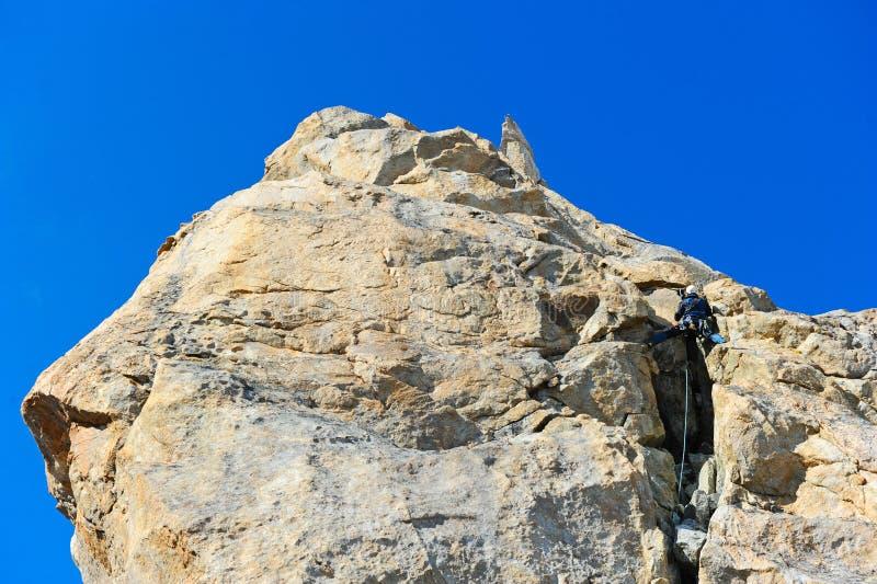 Escalador que alcanza la cumbre de la montaña imágenes de archivo libres de regalías