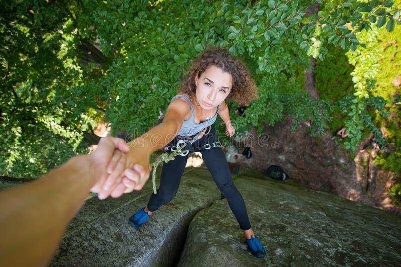 Escalador que ayuda al escalador femenino a alcanzar un pico de la montaña imagenes de archivo
