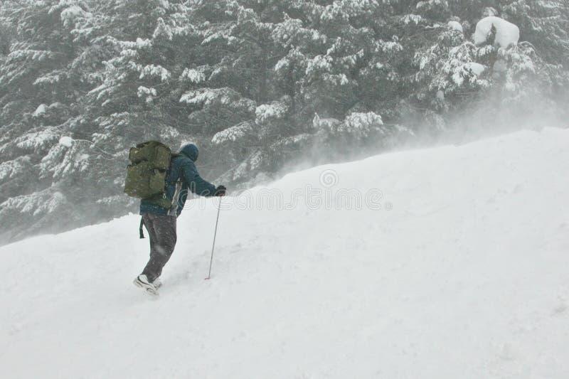 Escalador que va para la tapa en una tormenta de la nieve imagen de archivo