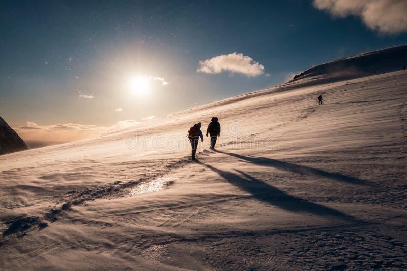 Escaladores con la mochila que sube en la montaña nevosa fotografía de archivo libre de regalías