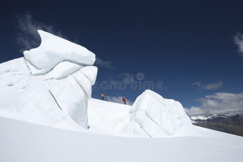 Escaladores de montaña que caminan más allá de formaciones de hielo foto de archivo libre de regalías