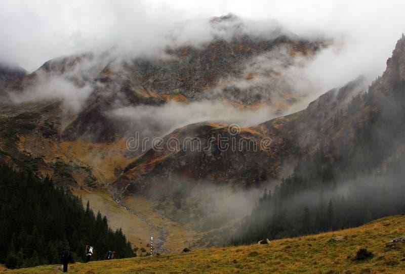 Escaladores en la manera encima de la montaña fotos de archivo